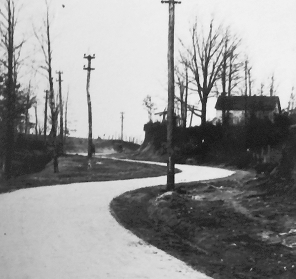 This black and white photograph, taken in 1918, depicts the Groveton School at the top of the hill on the right. The winding, curving road in the foreground is Route 1, which prior to straightening gave rise to this area being called Snake Hill.