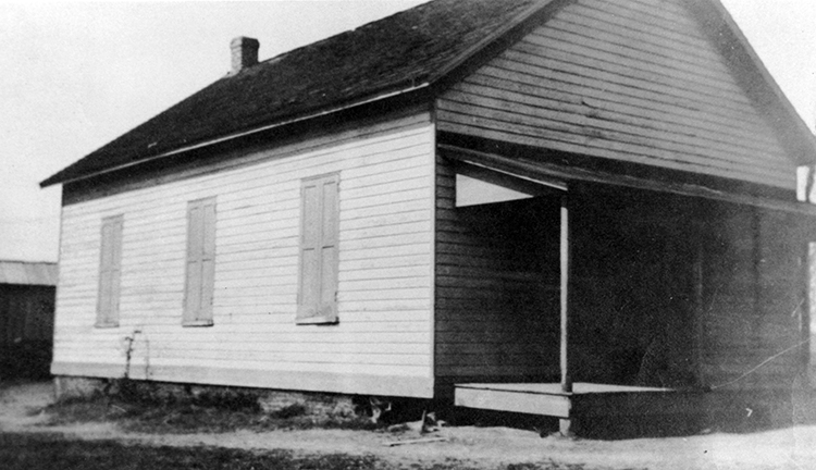 Black and white photograph of the Groveton School. The building is a small, one-story structure with a brick chimney in the rear. There is a porch and awning over the front entrance. The exterior siding has been painted white. There are three windows visible on one side, with wood shutters that are closed.