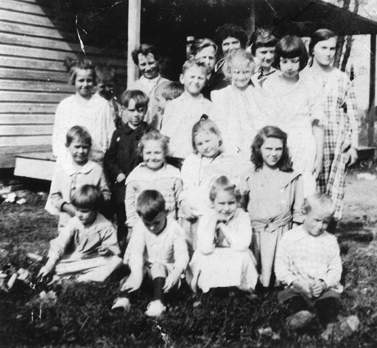 Black and white photograph of 18 children and their teacher posed in front of the Groveton School. The children are of various ages, some as young as age six and others in their teens.