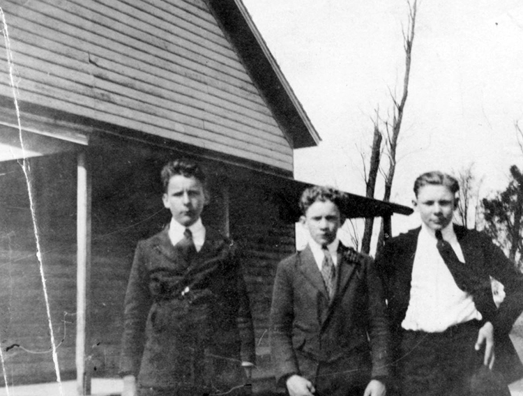 Black and white photograph of three boys standing in front of the Groveton School. They are dressed formally with white shirts, ties, and dark jackets.
