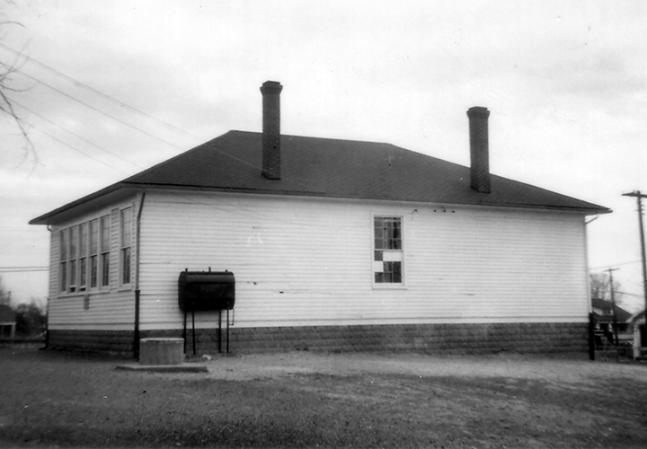 Black and white photograph of the two-room Groveton School. The rear of the building is shown. The school was heated by oil, and the oil reservoir can be seen on the side of the building. A cement well is located nearby.
