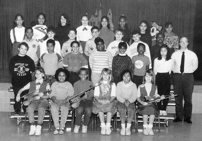 Black and white photograph of Groveton Elementary School's Strings musical performance group from the 1989 to 1990 yearbook. 28 children and one adult are pictured. The children are arranged in four rows on risers in front of the school's stage. The children in the first row are seated and are holding violins.