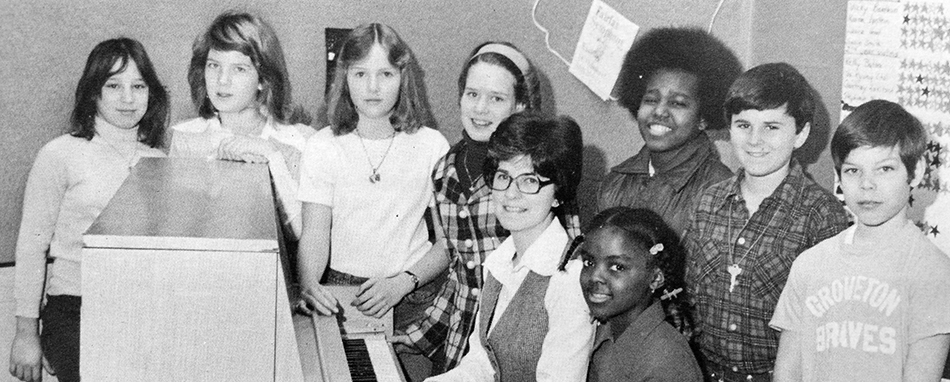 Black and white photograph of Groveton Elementary School's Choral Festival Group from the 1976 to 1977 yearbook. Eight children and one adult are pictured. The adult and one student are seated at an upright piano. The remaining students surround them.