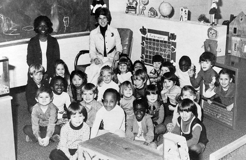 Black and white photograph from Groveton Elementary School's 1975 to 1976 yearbook showing students and teachers in the Apple Blossom kindergarten morning class. The children are seated on the floor in a classroom, and two teachers, sitting in chairs, are at the back of the group. 23 children are pictured.