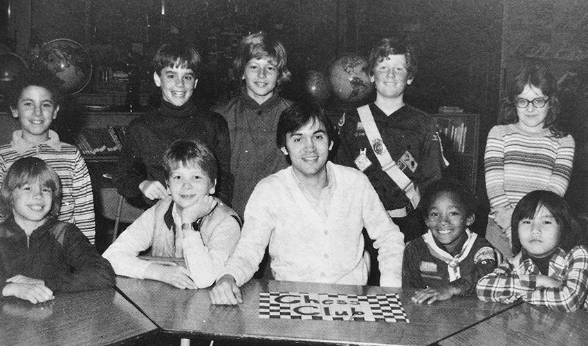 Black and white photograph of Groveton Elementary School's Chess Club from the 1980 to 1981 yearbook. Nine children and one adult are pictured. Four of the children and the adult are sitting at a table in what appears to be the library. There is a sign on the table in front of them that reads Chess Club. The sign has been decorated to look like a chess board.