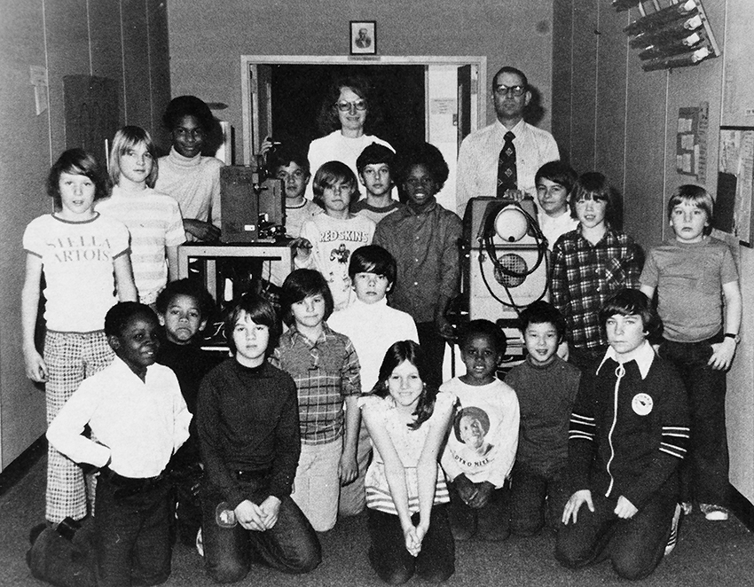 Black and white photograph of Groveton Elementary School's Audio-Visual Committee from the 1981 to 1982 yearbook. 19 children and two adults are pictured. They are posed next to a film projector on a cart and another, unidentified, piece of electronic equipment on a second cart. Some of the children are standing, others are kneeling on the floor. The two adults are visible in the far back.