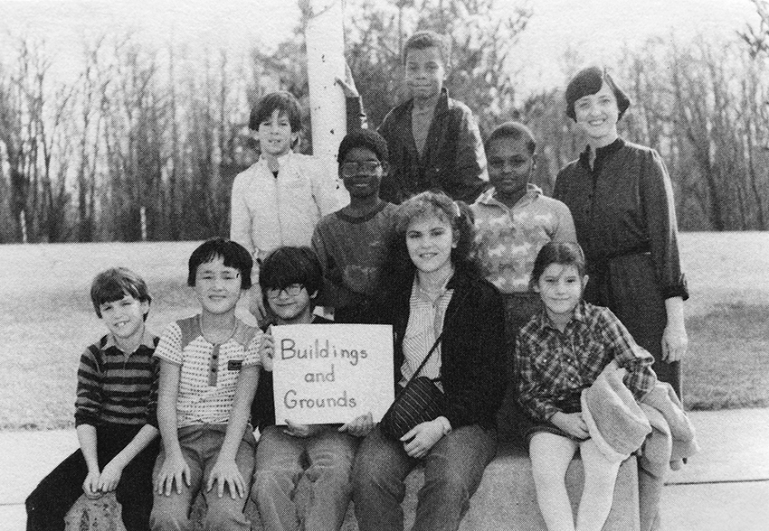 Black and white photograph of Groveton Elementary School's Building and Grounds Committee from the 1984 to 1985 yearbook. Eight children and two adults are pictured. They are seated outside next to the school's flagpole.