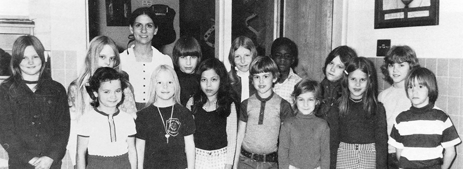Black and white photograph of Groveton Elementary School's Cafeteria Committee from the 1973 to 1974 yearbook. 14 children and one adult are pictured. They are standing inside the cafeteria near a doorway.