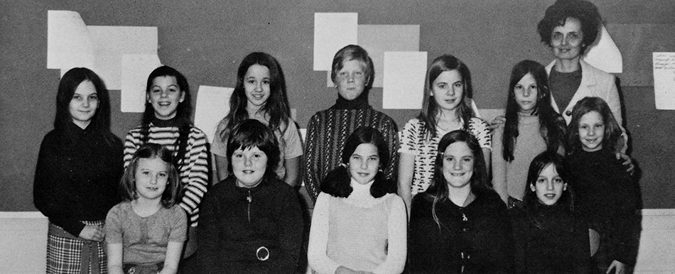 Black and white photograph of Groveton Elementary School's Library Committee from the 1972 to 1973 yearbook. 12 children and one adult are pictured.