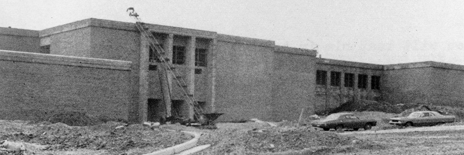 Black and white photograph from Groveton Elementary School's 1971 to 1972 yearbook showing construction progress on the new Groveton School. The original main entrance of the building is shown. The building is a two-story brick structure. Construction equipment is visible near the school's entrance, and two cars are parked in front of the building. The grounds have yet to be landscaped and there are mounds of dirt visible in the foreground.