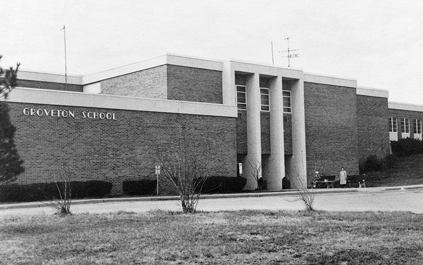 Black and white photograph of Groveton Elementary School taken in 1983. The original main entrance to the building is shown. Two adults, possibly senior citizens, are seated on benches near the main entrance.