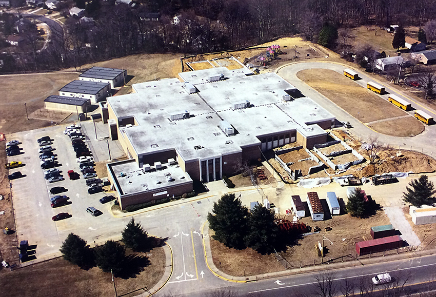 Aerial photograph of Groveton Elementary School, taken from above Harrison Lane looking toward the school from the east. Several trailers are visible behind the building. The foundations have been laid and cinderblock walls are going up on additional classroom wings on the east and west sides of the building. A portion of the driveway near the old main entrance is blocked off and construction trailers and equipment are staged in this area.