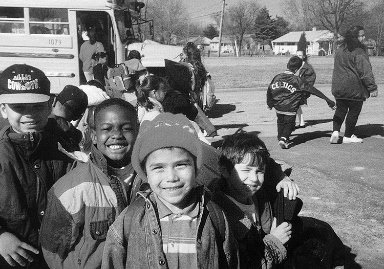 Black and white photograph of students waiting to board a school bus during the 1993 to 1994 school year. Four boys at the back of the line have turned around and are smiling broadly for the camera. They are wearing coats and hats. There are no leaves on the trees in the background, and several houses are visible in the far distance.