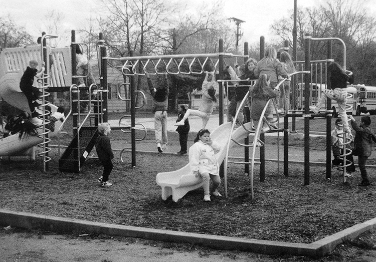 Black and white photograph of the new playground equipment. There is a spiral-shaped slide, spiral ladder, monkey bars, a curved slide, a curved ladder, and two raised platforms. 16 children are visible playing on the equipment. Two school buses are parked in the far distance.