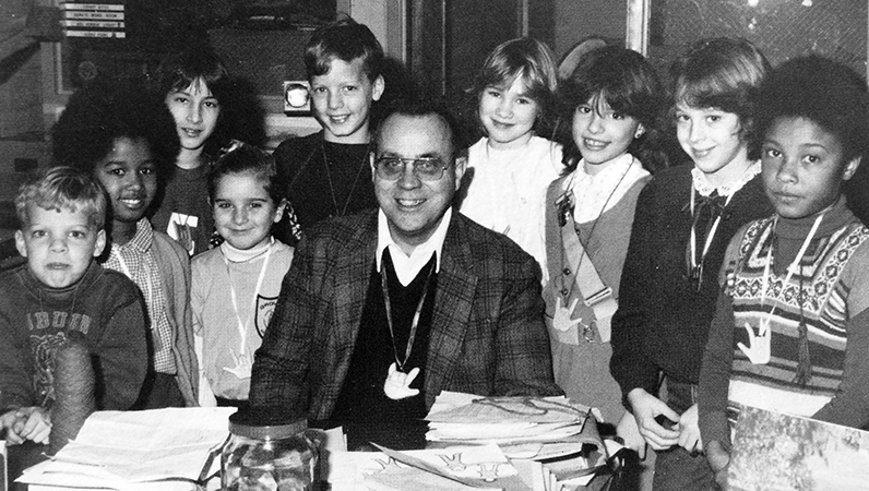 Black and white photograph of Principal Bill Zepka taken in 1981. He is seated at his desk in the library and is surrounded by a large group of smiling students. Nine children are pictured.
