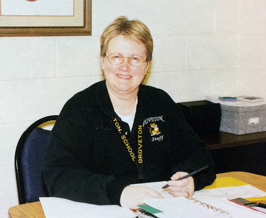 Color photograph of Principal Henderson taken during the 1997 to 1998 school year. She is seated at a table and is looking up from the paperwork in front of her. A pen is in her left hand.