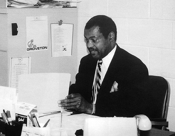 Black and white photograph of Principal Thompson seated at his desk. He is looking through paperwork.