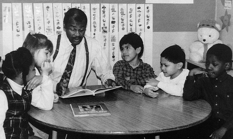 Black and white photograph Principal Thompson reading to a group of students. Five children, three boys and two girls, are seated with Thompson at a small round table in a classroom.