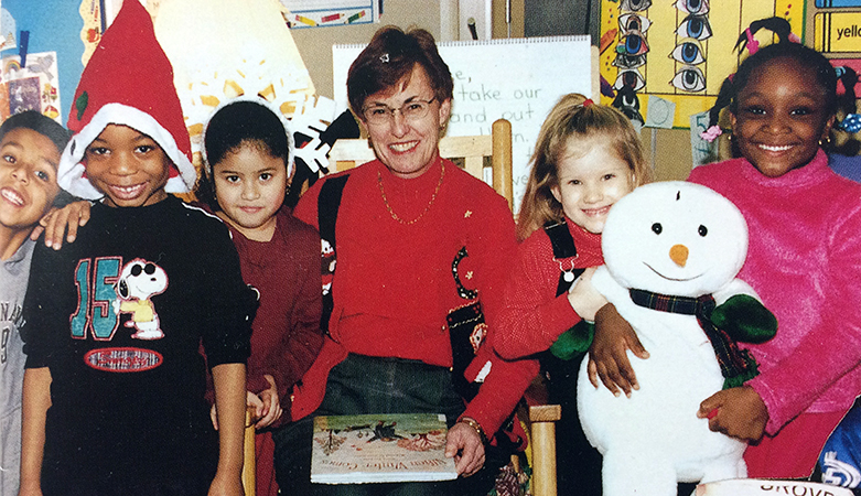Color photograph of Principal Lamb taken during the 2002 to 2003 school year. She is seated on a brown rocking chair in a classroom with a closed picture book on her lap. She is surrounded by a group of five smiling children, two boys and three girls. Two of the girls, on Lamb's right, are holding a stuffed snowman figure.