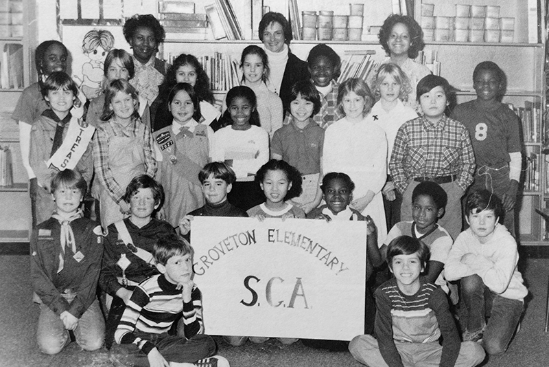 Black and white photograph of Groveton Elementary School's Student Council from the 1980 to 1981 yearbook. 23 children and three adults are pictured. Three students are holding up a sign that reads Groveton Elementary SCA.