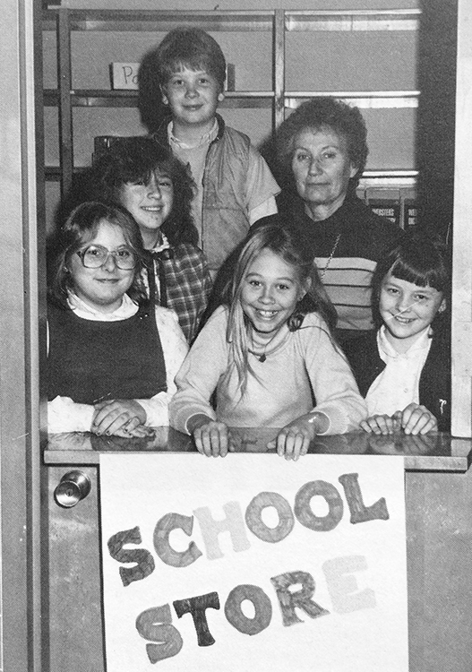 Black and white photograph of Groveton's School Store Committee from the 1980 to 1981 yearbook. Five children and one adult are pictured. They are standing inside the school store. The door to the store is a Dutch door, with a top half that opens separately. The top half is open and the bottom is closed. A girl in the center is holding a sign in front of the door that reads School Store.