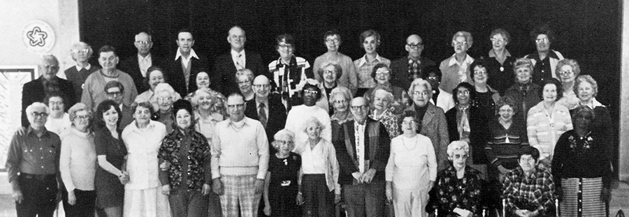 Black and white photograph of some of the senior citizens who took part in the nutrition program during the 1976 to 1977 school year. 48 people are in the picture. They are standing in four rows in front of the school stage. Two ladies are seated in chairs in the foreground.