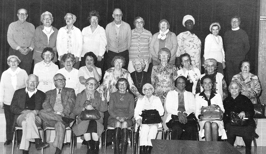Black and white photograph of some of the senior citizens who took part in the nutrition program during the 1980 to 1981 school year. 28 people are in the picture. They are arranged in three rows on, and in front of, the school's stage.