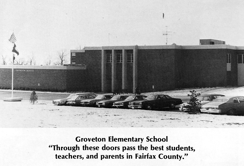 Black and white photograph of Groveton Elementary School from the 1974 to 1975 yearbook. There is a light covering of snow on the ground. The original main entrance to the building is pictured. The entrance was moved during a subsequent renovation. The photograph has a caption that reads: Groveton Elementary School - Through these doors pass the best students, teachers, and parents in Fairfax County.